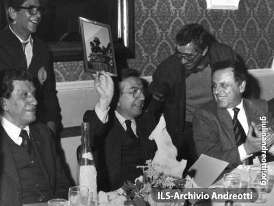 Serata del Marcia club Lazio. Andreotti, seduto fra il fratello Francesco e il giornalista Paolo Valenti, mostra divertito la foto di una sua caricatura al corteo dei carri carnevaleschi di Viareggio