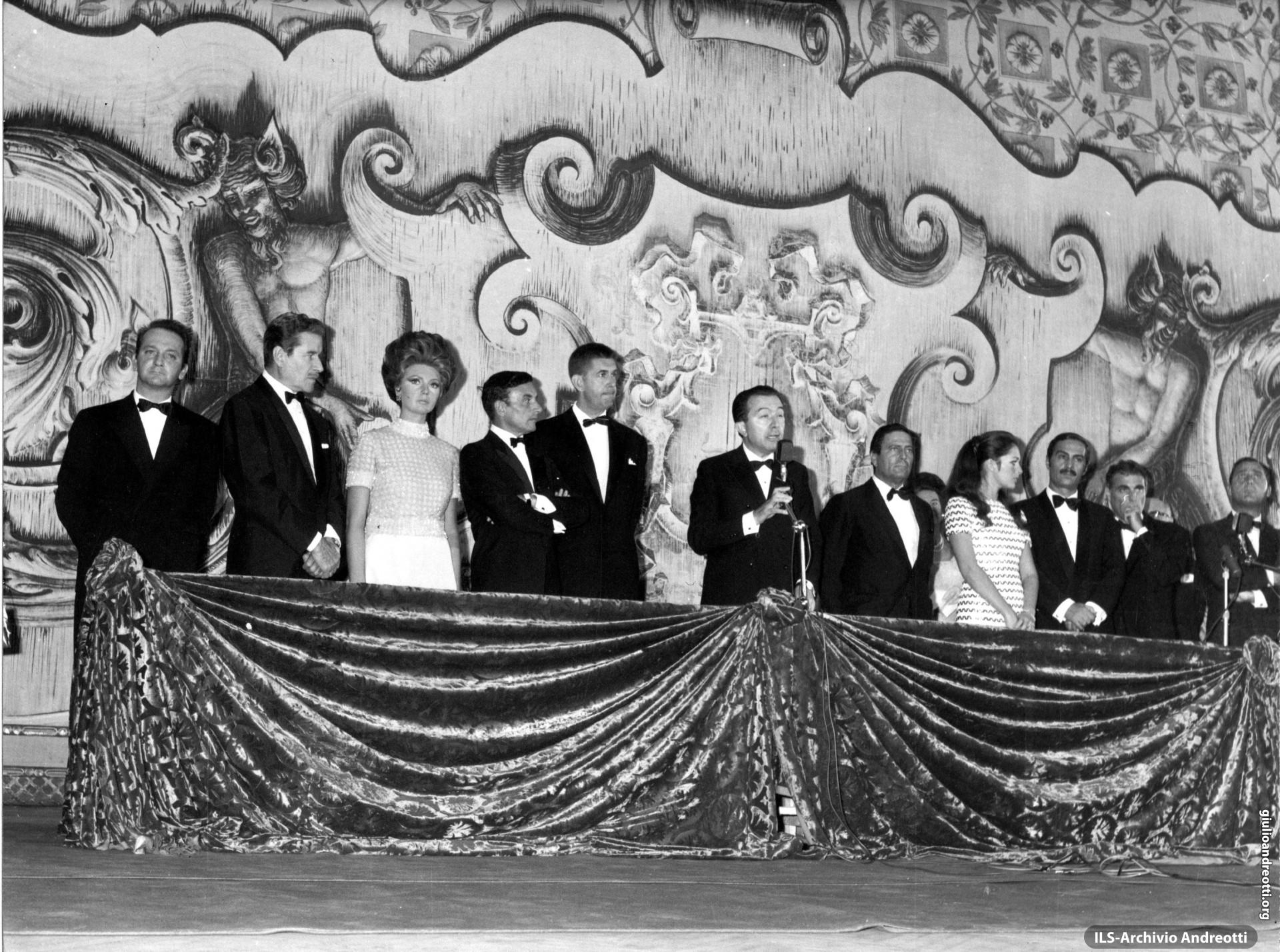 Affiancato da grandi protagonisti del cinema italiano, Andreotti parla dal palco reale del Teatro San Carlo di Napoli alla conclusione delle Giornate del Cinema di Sorrento. E' il 30 settembre 1968.